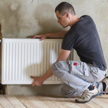 plumber installing heating radiator